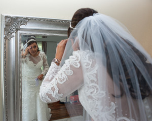 Latina bride checking details in the mirror.