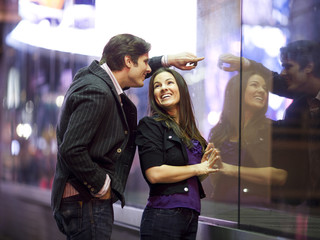 USA, New York City, Manhattan, Times Square, Young couple standing text to window display