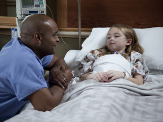 USA, Utah, Payson, Male nurse talking to girl (8-9) lying on hospital bed