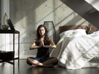 Woman practicing yoga in her bedroom at home