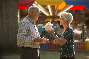 Happy fun couple sharing cotton candy snack at amusement park fun fair