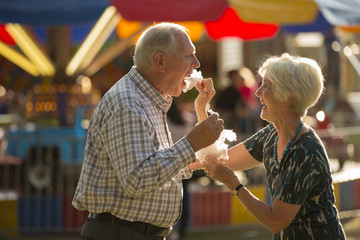 Happy fun woman feeding husband cotton candy snack at amusement park fun fair