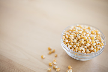 Bowl of pop corn kernels on wooden table