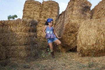 Niña pequeña en las alpacas de heno al final de verano. Chica joven disfrutando en el campo de una tarde de verano.