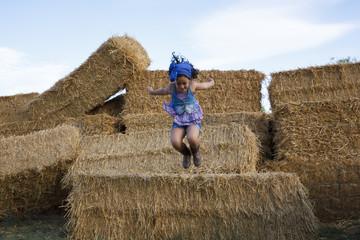 Niña pequeña saltando. Chica joven disfrutando en el campo de una tarde de verano.