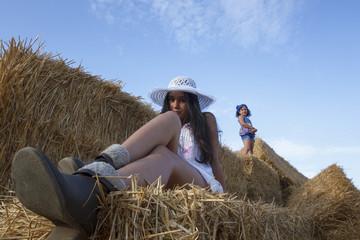 Niña pequeña y adolescente en las alpacas de heno al final de verano. Dos hermanas disfrutando en el campo de una tarde de verano.