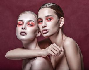 Portrait of two beautiful young women with bright fashion makeup