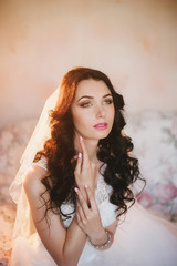 Portrait of a beautiful young brunette bride, smiling, boudoir, fees hairstyle, make-up, wedding, lifestyle