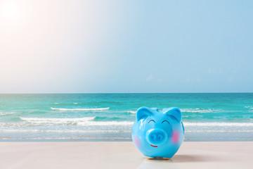 summer blue piggy bank on the beach.