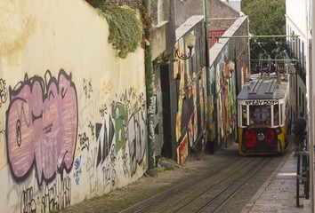 Lavra Funicular going up in the narrow street full of graffiti, Lisbon