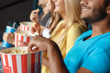 Friends eating popcorn at the movie theatre