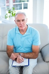 High angle view of thoughtful senior man with clipboard