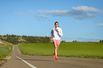 Sporty motivated woman running on country side road. Female athlete training outdoor.