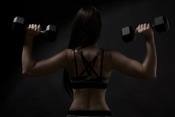 strong tanned beautiful sports girl on a black background. copy space.