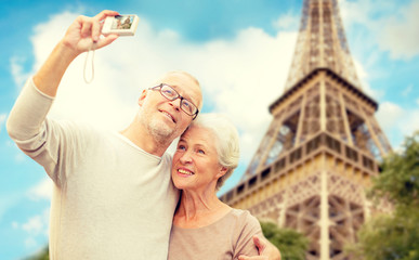 senior couple with camera over eiffel tower