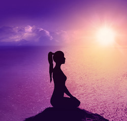 Yoga and meditation. Silhouette of woman on the beach