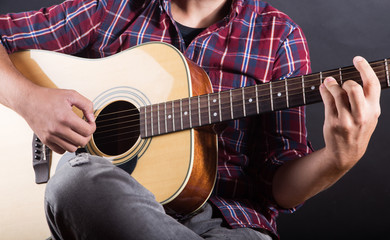 young man playing an acoustic guitar in studio