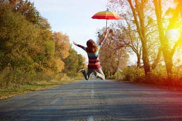 Picture of jumping lady holding umbrella with arms sideways
