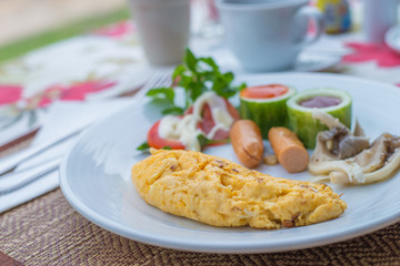 Omelet with vegetable salad and hot dogs on white plate.