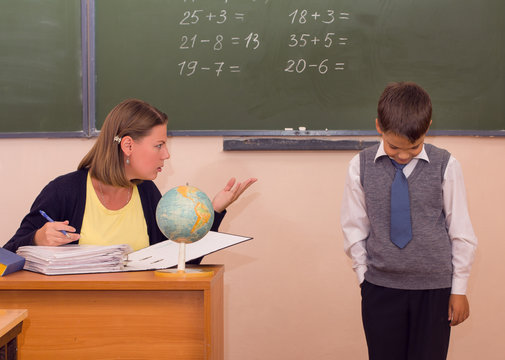 The teacher scolds a little schoolboy in a classroom.
