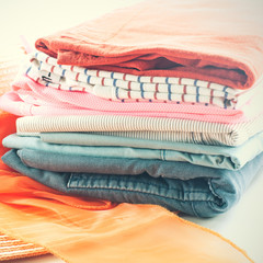 Pile of colorful clothes and Beautiful summer hat over white bac