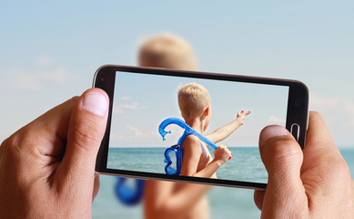 Male hand taking photo of a Boy holding snorkeling mask and prepare to dive in with cell, mobile phone. Kid on the beach in front of the sea showing something above.  Active summer holiday vacation