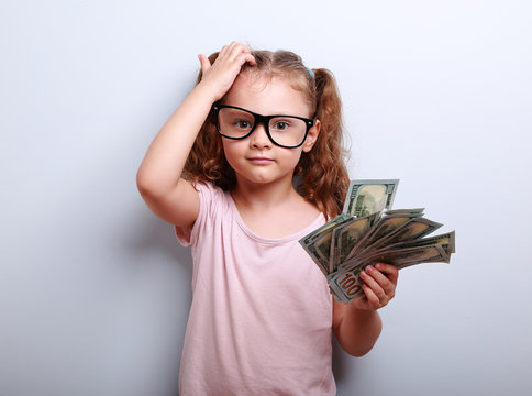 Small professor in eye glasses scratching head, holding money an
