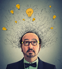 Thinking man with question signs and light idea bulbs above head looking up