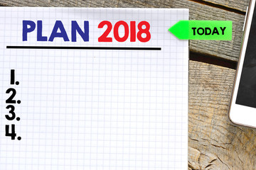 Plan 2018  on paper sheet with mobile phone  on wooden background