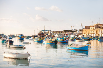 Colorful typical boats in Mediterranean traditional fisherman village. Marsaxlokk, Malta.