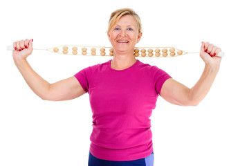 Happy and smile old senior woman dressed in t-shirt color Marsala doing sport fitness exercises with manual wooden masseur for massage of a neck, isolated on white background, Positive emotions