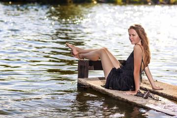 Sexy Sensual Caucasian Blond Woman Sitting on Pier Near Water. R