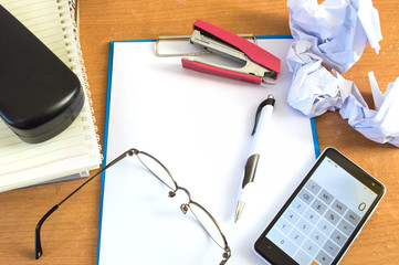 Office desk with supplies calculator pen book and glasses