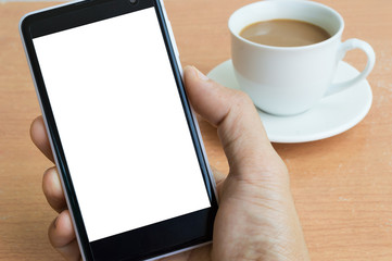 Hand holding a phone with the background of coffee cup on the ta