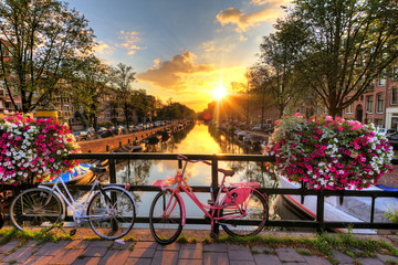 Spoed Fotobehang Amsterdam Beautiful sunrise over Amsterdam, The Netherlands, with flowers and bicycles on the bridge in spring