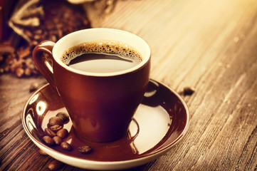 Cup of aromatic coffee over wooden table. Coffee beans