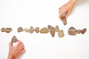 Hände bilden Linie aus vielen Steinen