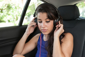 Young woman in back seat of car with black headphones