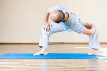 Inspired asian man doing exercise of yoga indoor