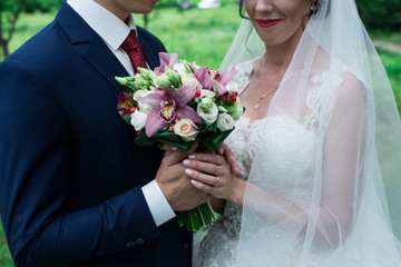 Bride and groom holding hands with bouquet. Wedding.
