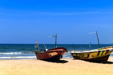Two fishing boats on the beach by ocean