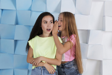 Blond girl whispering something interesting in brunette's ear, girls wearing jeans shorts and bright colored t-shirts