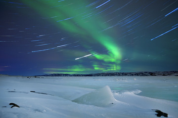 Aurora borealis over snowy winter landscape, northern Norway