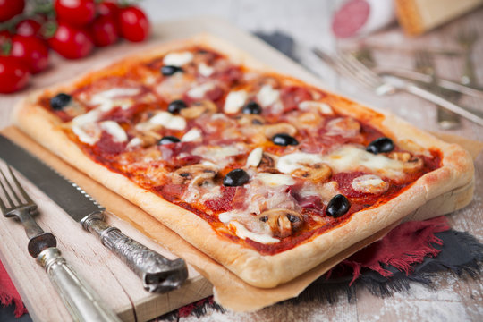 Homemade rectangular pizza on a rustic table with ingredients