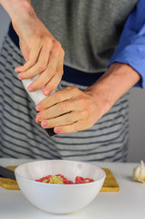 Man hands making stuffing for dumplings with meat