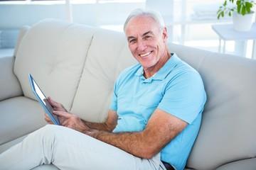 Portrait of happy senior man using digital tablet