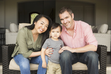 Smiling man and woman sitting side by side on a sofa, posing for a picture with their young son.