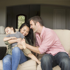 A family, a man and woman sitting side by side on a sofa  playing with their young son.