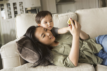 Woman lying on a sofa, smiling, cuddling with her young son and looking at a cell phone.
