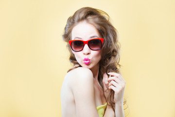 Attractive surprised young woman wearing sunglasses on gold back